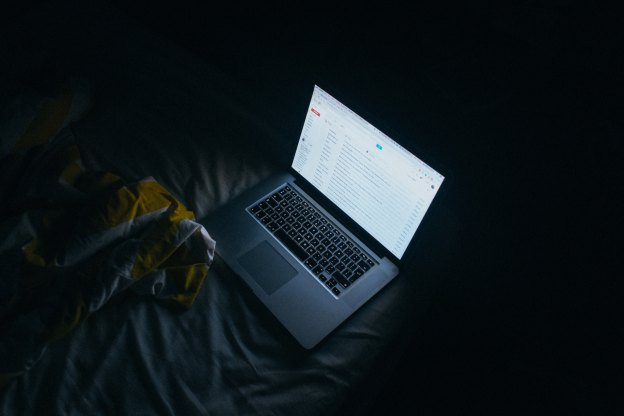 A MacBook Open In A Dark Room